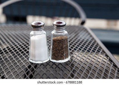 Classic glass salt and pepper shakers on a metal grate table at a patio of a restaurant.