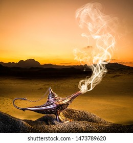 classic gold-colored aladdin lamp laid on the sand of a dune with smoke coming out. desert in the background.