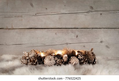 classic golden Christmas tealight holder with burning candles, on sheepskin and weathered wooden background