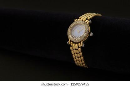 Classic Golden women wrist watch with precious stones on dark background