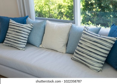 classic gray sofa and navy blue pillows by the window in living corner