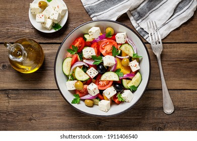Classic Greek salad with fresh vegetables, feta cheese and  olives. Healthy food. Wooden background. Top view