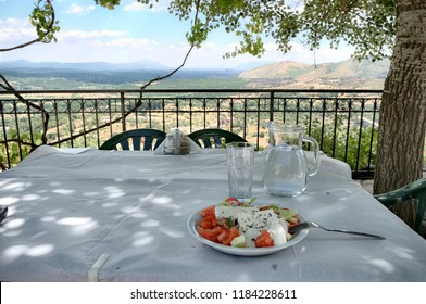 classic greek salad on table under the shadow of a tree