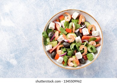 Classic Greek salad from shrimps, tomatoes, cucumbers, red pepper, onion with olives, oregano and feta cheese. Top view. Copy space.
