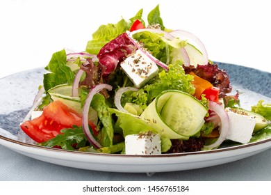 Classic Greek salad of tomatoes, cucumbers, red pepper, onions with olives, oregano and feta cheese. On a decorative plate