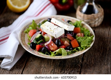 Classic Greek salad from tomatoes, cucumbers, red pepper, onion with olives, oregano and feta cheese.