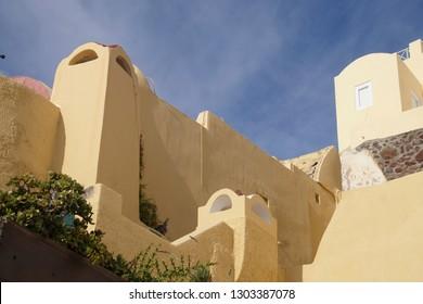 Classic Greek stucco buildings on the slopes of the volcano caldera in Oia, Santorini, Greece