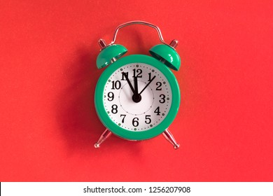 Classic green alarm clock on red background. Copy space.