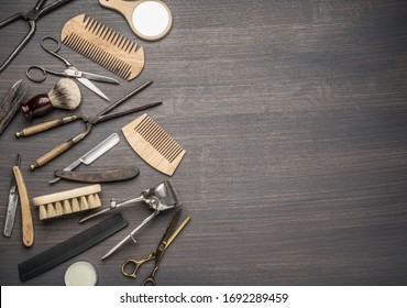 Classic grooming and hairdressing tools on wooden background. Top view on barbershop instruments  laying on dark wooden table.