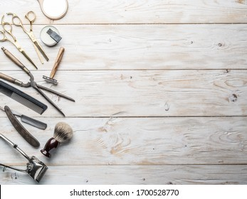 Classic grooming and hairdressing tools on wooden background. Top view on barbershop instruments  laying on white wooden table.