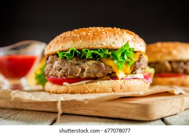 Classic hamburger with beef and sauce on dark background.