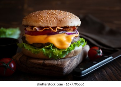 Classic hamburger with cheese, bacon, tomato and lettuce on dark wooden background