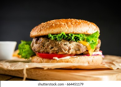 Classic hamburger with tasty beef, tomato, salad and cheese on dark background. American food