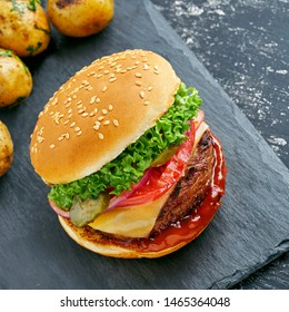 Classic hamburger with tomato, lettuce and onion served with grilled potatoes and broccoli on a black stone board. Top view, directly above.