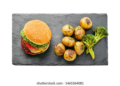 Classic hamburger with tomato, lettuce and onion served with grilled potatoes and broccoli isolated on white background. Top view, directly above.