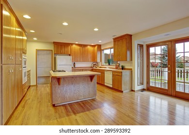 Classic hardwood kitchen with connected living room and back door.