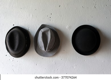 Classic hats on white wall. Black and grey Bowler felt trilby/fedora Hats