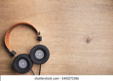 classic headphones on wooden background with copy space for text