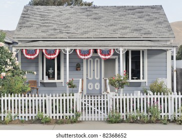 Classic historic american colonial era wooden house with white picket fence and flag