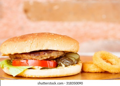 Classic homemade hamburger with onion rings on a wooden plate. Juicy homemade food. Horizontal, macro