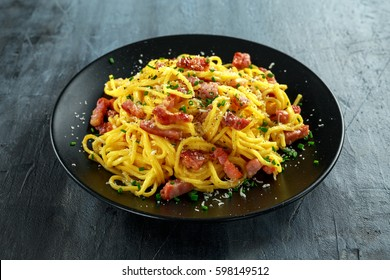 Classic Homemade Pasta carbonara Italian with Bacon, eggs, Parmesan Cheese on black plate