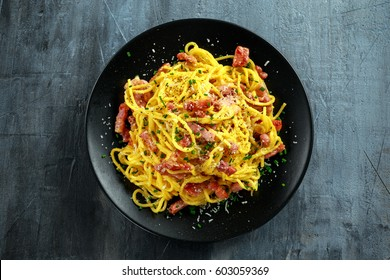 Classic Homemade Pasta carbonara Italian with Bacon, eggs, Parmesan Cheese on black plate.