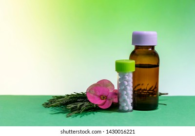 Classic Homeopathic Concept - Close up image of homeopathic medicine with globule pills and brown liquid bottle with pink flower petal on green shrub isolated and mint background