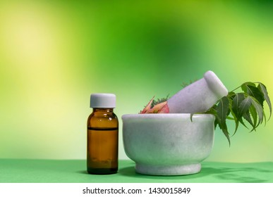 Classic Homeopathic Concept - Healing herbs, pink flower in mortar with homeopathic substance in brown bottle on green mix yellow background