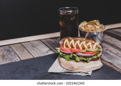 Classic hot dog with chips and soft drink on dark background. Tabletop, front view.