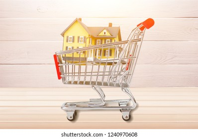 Classic house model  in shopping cart on backgrouund