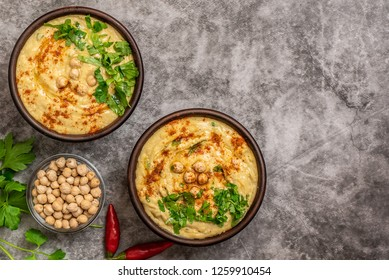 Classic hummus in bowls on a grey background. With copy space. Top view.