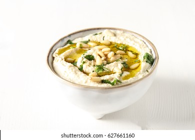 Classic hummus with herbs, olive oil in a vintage ceramic bowl. Traditional Middle Eastern cuisine. Light white background