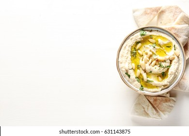 Classic hummus with herbs, olive oil in a vintage ceramic bowl and pita bread. Traditional Middle Eastern cuisine. Light white background