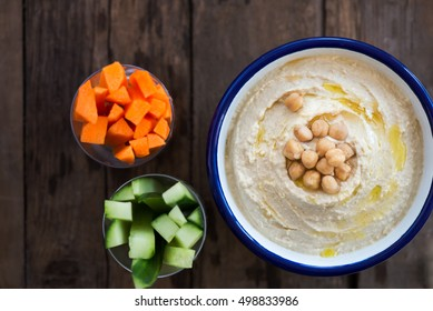 Classic Hummus made from Chickpeas in White Bowl, Carrot and Cucumber Sticks nearby, Wooden Rustic Background, top view