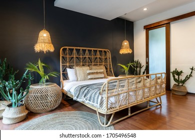 Classic interior bedroom at house with ethnic decor, lamps over bedside tables, wicker headrest at comfortable bamboo bed, carpet or rug and exotical cactus plant in basket near blue copy space wall