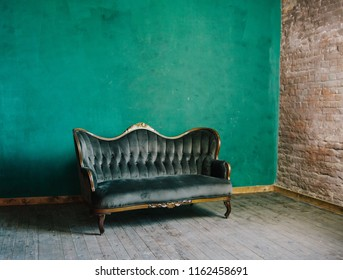 classic interior in dark green colors. vintage velvet sofa near emerald wall. Armrest of luxurious green sofa, close-up. Luxury vintage green couch in the room. Antique wood sofa couch.