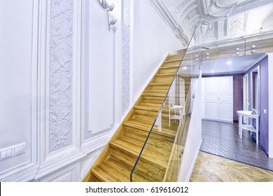Classic interior design duplex apartment with white wall and ceiling moldings. Design of stairs in a rich house.