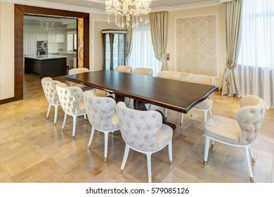 Classic interior of dining room in brown, white, beige colors, with crystal chandelier in the center of ceiling and wooden table. Many chair around table, room for big family.