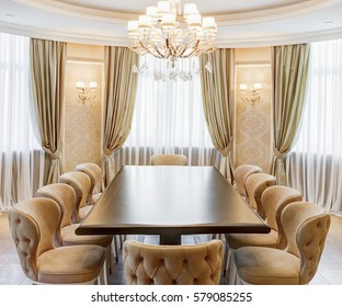Classic interior of dining room in brown, white, beige colors, with crystal chandelier in the center of ceiling. Long wooden table and many chairs around, room for big family.
