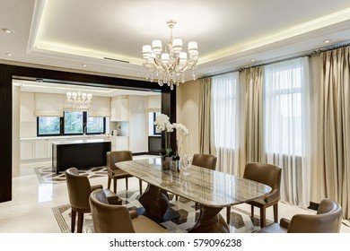 Classic interior of dining room in brown, white, beige colors, with crystal chandelier in the center of ceiling. Wooden table and many chairs around.View of other room with kitchen bar.