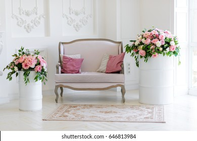 Classic interior with an exquisite sofa and decoration of beautiful flowers Exquisite sofa in a white interior with beautiful bouquets of flowers from roses, peony and green leaves