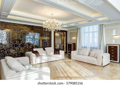 Classic interior of living room in brown, white, beige, with glasses wall and crystal chandelier in the center of ceiling. Three big and cozy sofas with pillows for big family.