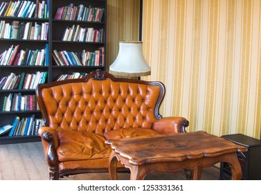 Classic interior room with books. Old antique leather arm chairs, table and bookshelves. Classic decoration with elegant furniture. Details.