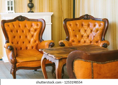 Classic interior room. Old antique leather arm chairs and table. Classic decoration with elegant furniture. Details.