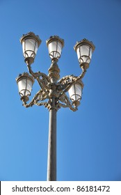 Classic iron lamppost over a blue sky