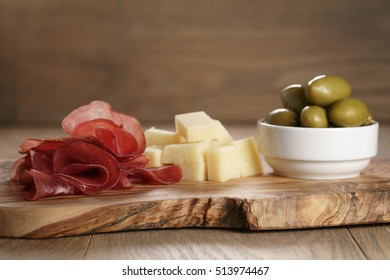 classic italian antipasti, breasola. olives and parmesan on olive board, shallow focus