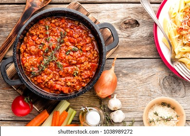 classic italian bolognese sauce stewed in stewpot with ingredients on wooden table, top view