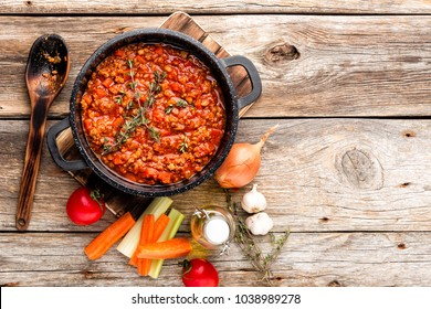classic italian bolognese sauce stewed in stewpot with ingredients on wooden table, top view, culinary background with space for text