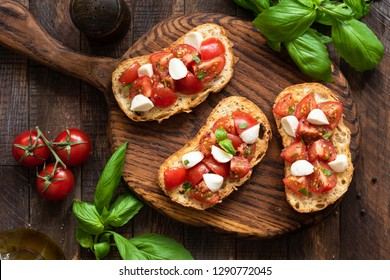 Classic italian Bruschetta with tomato mozzarella cheese on wooden serving board. Table top view. Antipasto, appetizer