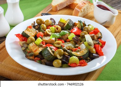 classic Italian Caponata with aubergine, green olives, capers, celery and herbs on white plate on wooden cutting board with red vine vinegar and bread, view from above, close-up